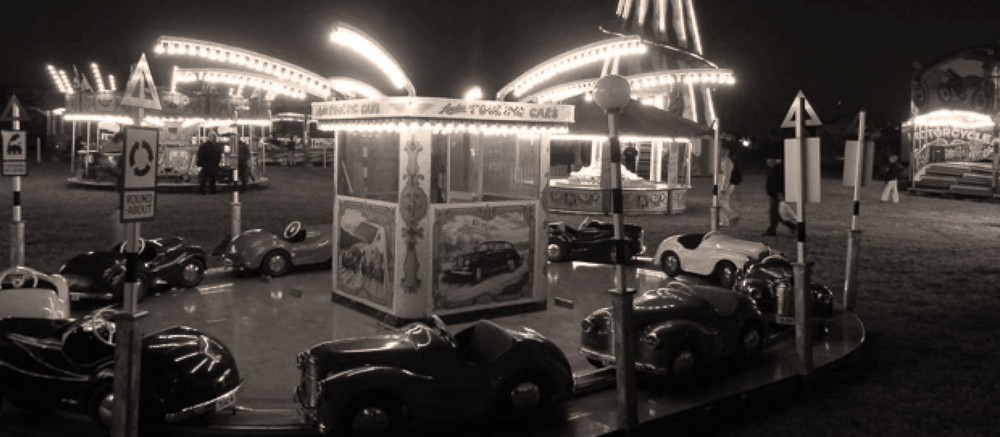 goodwood revival historic motorsport and aviation event sepia image, vintage funfair at night